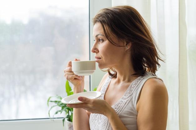 Mujer madura bebe café por la mañana