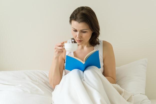 Mujer madura, en cama, libro de lectura