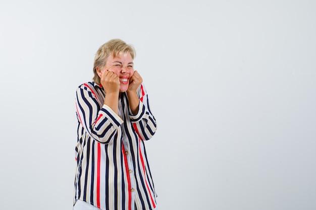 Mujer madura en una camisa de rayas verticales