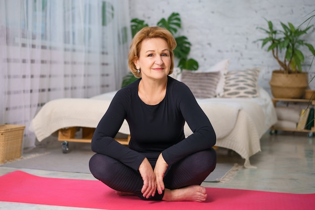 Mujer madura en un chándal negro haciendo yoga sentado en la estera en casa