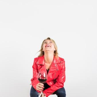 Mujer madura en la chaqueta roja que sostiene la copa de vino que mira para arriba que ríe contra el contexto blanco