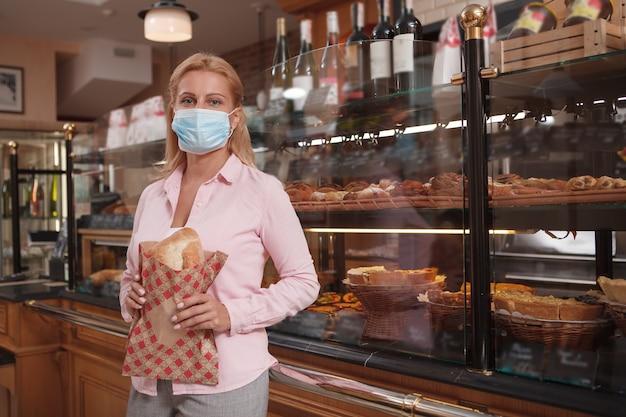 Mujer madura comprando pan durante la pandemia de coronavirus, con mascarilla