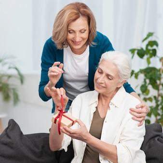 Mujer madura dando un regalo a su amiga