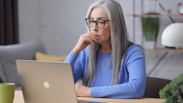 Mujer madura deprimida recibió malas noticias en línea. síndrome de burnout, exceso de trabajo, depresión.