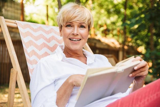 Mujer madura emocionada leyendo un libro