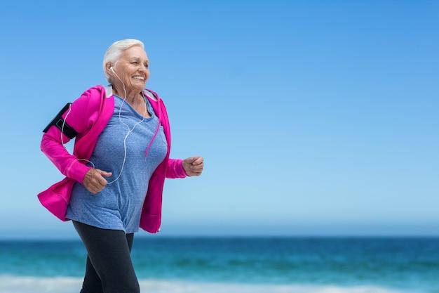 Mujer madura enfocada corriendo y escuchando música