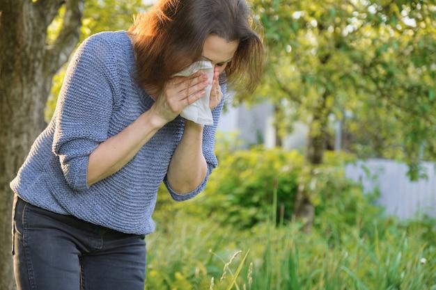 Mujer madura estornudando en pañuelo, alergia al polen, resfriados