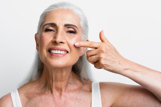 Mujer madura feliz que aplica la crema