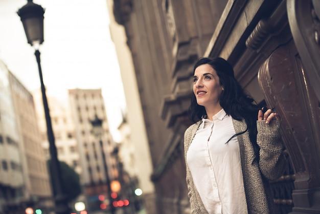 Mujer madura, feliz y segura de sí misma caminando por las calles de una ciudad europea.
