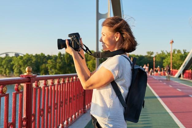 Mujer madura fotografiando con cámara, periodista fotográfico, blogger de viajes