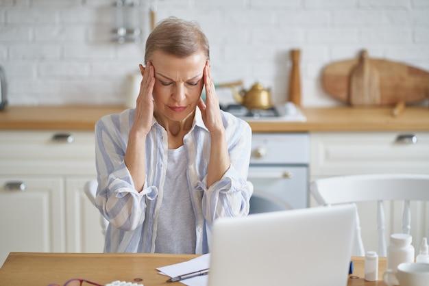 Mujer madura frustrada que sufre de dolor de cabeza mientras trabaja en línea desde casa