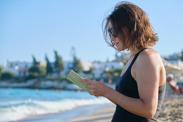 Mujer madura con gafas de sol y traje de baño relajante libro de lectura y disfrutando del atardecer del mar