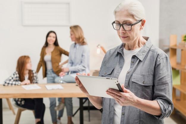 Mujer madura con gafas sosteniendo una tableta