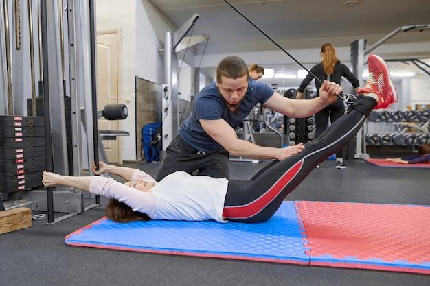 Mujer madura haciendo ejercicio en simuladores de descompresión con rehabilitación de entrenador