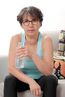 Mujer madura hermosa fitness con botella de agua