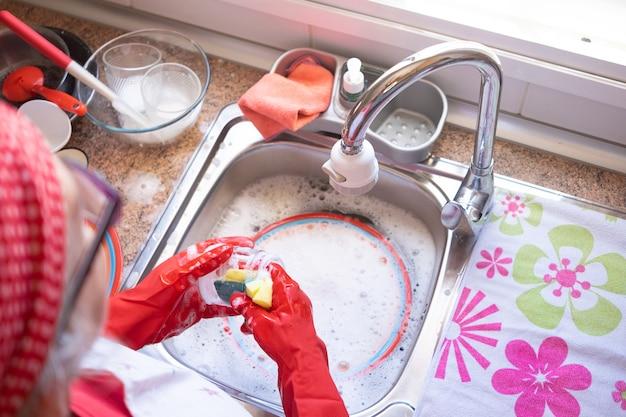 Mujer madura lavando vajilla y cubertería delante de la ventana con guantes rojos