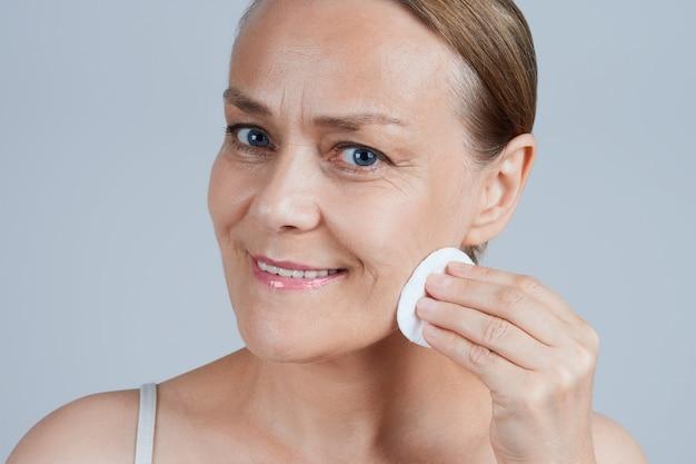 Mujer madura limpia su cara con un algodón. cuidado cosmético en la vejez.