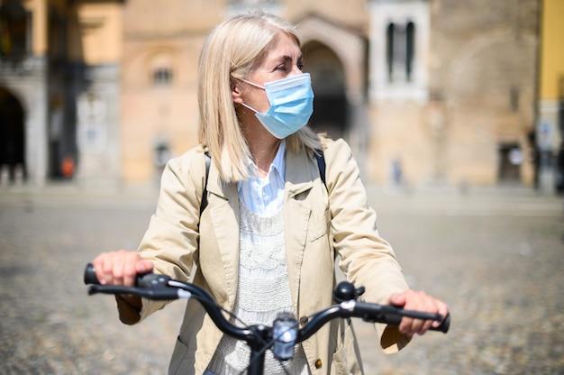 Mujer madura con máscara médica facial mientras monta una bicicleta durante la cuarentena al aire libre