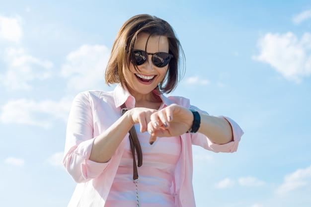 La mujer madura mira el reloj, la emoción de la alegría.