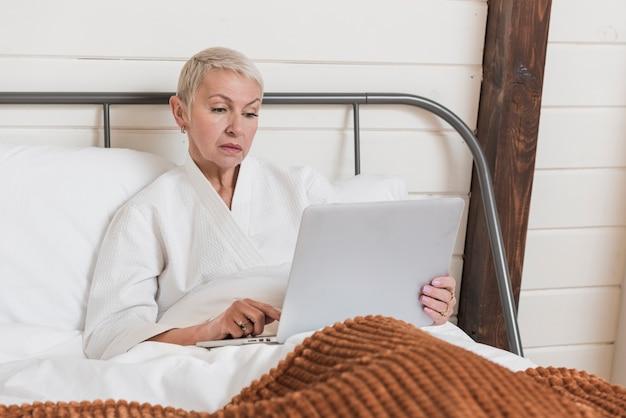 Mujer madura mirando en una computadora portátil en la cama