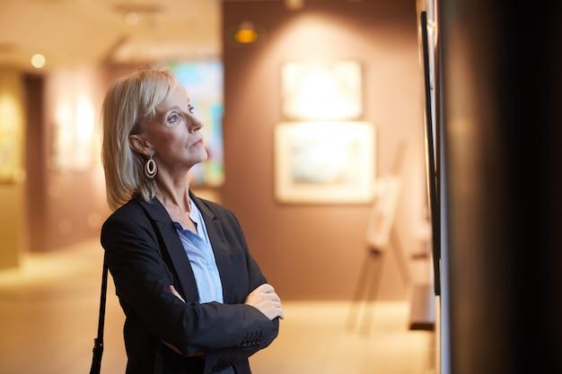 Mujer madura mirando pinturas en la galería de arte
