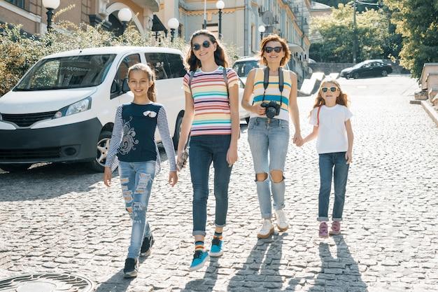 Mujer madura con niños caminando en una calle de la ciudad en un día soleado de verano