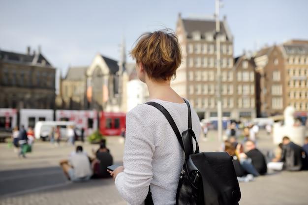 Mujer madura de pie en un soleado día de otoño en la plaza central de la presa en la ciudad vieja de amsterdam. turismo y viajes.