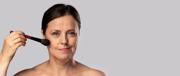 Mujer madura con pincel de maquillaje en el rostro con espacio de copia