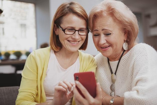 Mujer madura que encuentra a su madre mayor en la cafetería