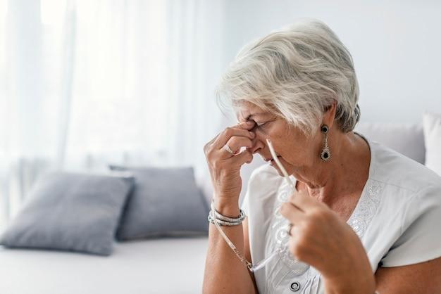 Mujer madura que se sienta en un sofá blanco en una casa que toca su cabeza con sus manos mientras que havi