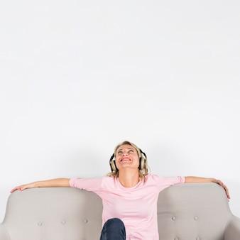 Mujer madura que se sienta en el sofá que disfruta de la música en el auricular contra el fondo blanco