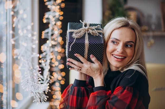 Mujer madura con regalo de navidad por bthe ventana
