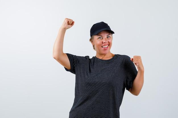 Mujer madura rubia con una camiseta negra y una gorra negra
