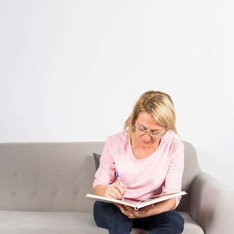 Mujer madura rubia que se sienta en la escritura del sofá en diario con la pluma