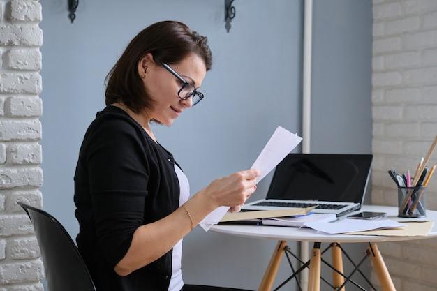 Mujer madura sentada en su escritorio con documento de carta en papel