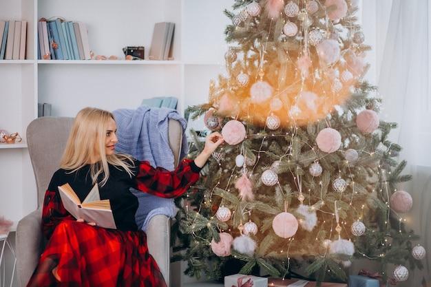 Mujer madura, se sentar en silla, por, árbol de navidad