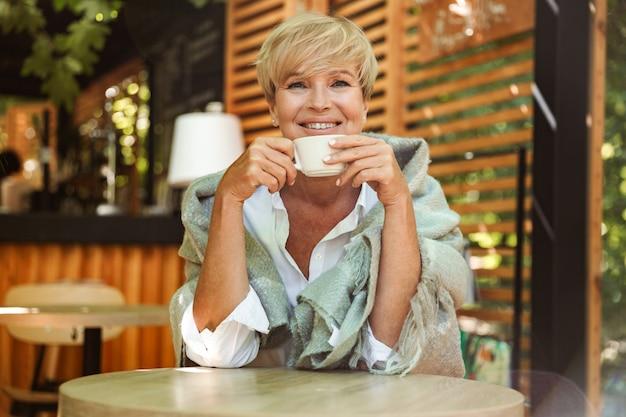 Mujer madura sonriente envuelta en una manta