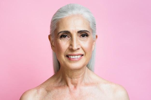 Mujer madura sonriente con fondo rosa