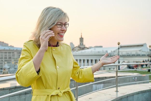 Mujer madura sonriente en gafas, abrigo amarillo hablando por teléfono móvil