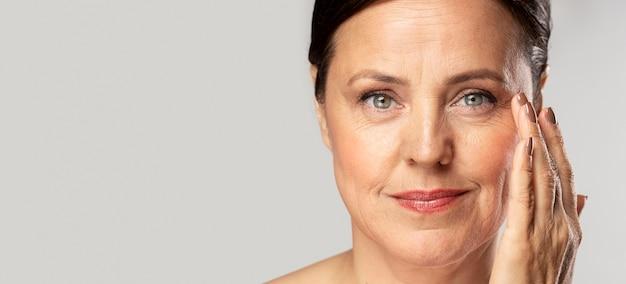 Mujer madura sonriente con maquillaje posando con la mano en la cara y copie el espacio