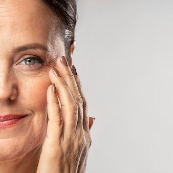 Mujer madura sonriente con maquillaje posando con la mano en la cara