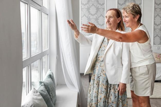 Mujer madura sonriente mostrando algo desde la ventana
