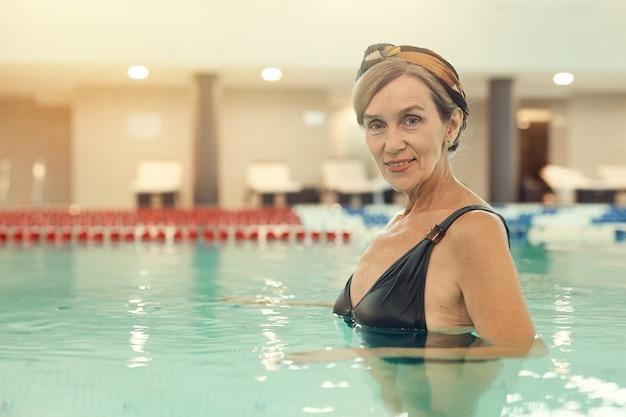 Mujer madura sonriente en piscina