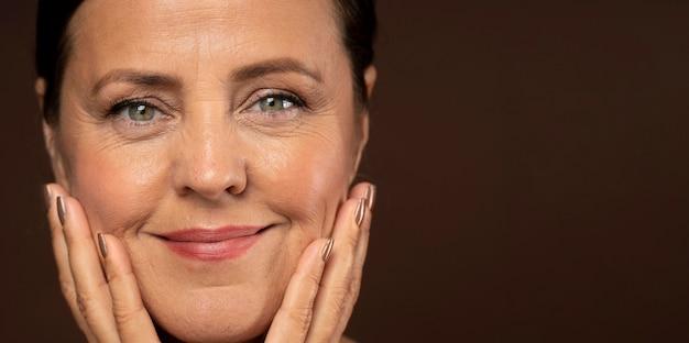 Mujer madura sonriente posando con maquillaje en