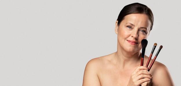 Mujer madura sonriente posando con pinceles de maquillaje y espacio de copia