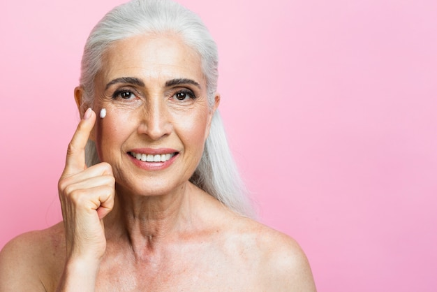 Mujer madura sonriente que aplica la crema hidratante