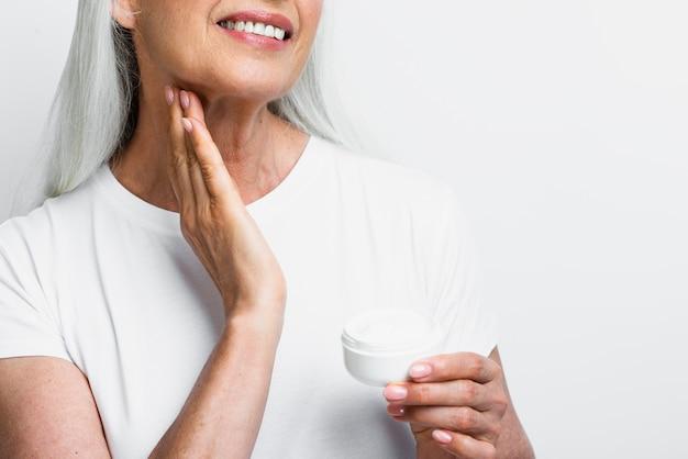 Mujer madura sonriente que aplica el tratamiento