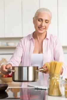 Mujer madura sonriente que se coloca en la cocina que cocina