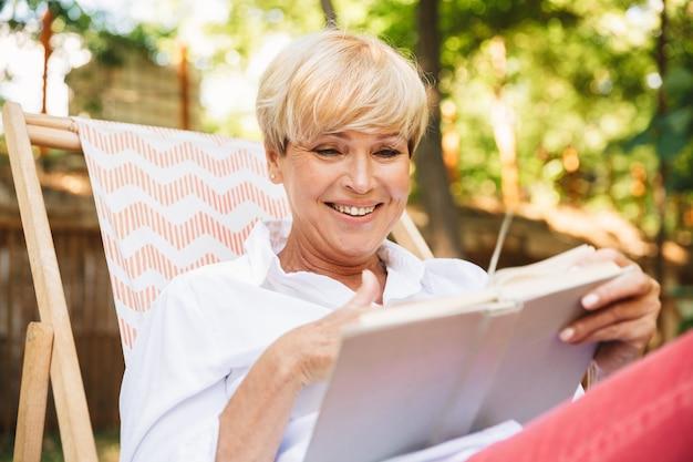 Mujer madura sonriente que lee un libro mientras descansa