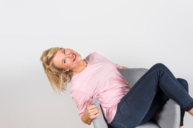 Mujer madura sonriente que se sienta en la silla del brazo contra el contexto blanco
